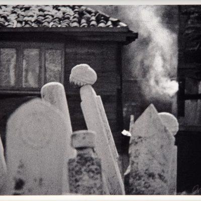 Ara Güler, Ayvansaray Eyüp arasında bacası tüten eski bir ev ve mezar taşları, 1964, 44x63 cm.